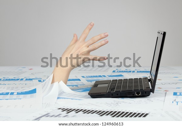 Drowning in paperwork concept. White collar worker reaching out after computer - rescue of paperwork.