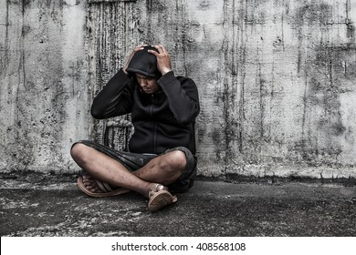 Drug abuse concept., overdose asian male drug addict with problems, man in hood with hands on his head