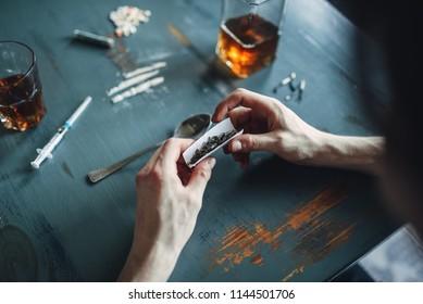 Drug addict hands prepares a dose, top view