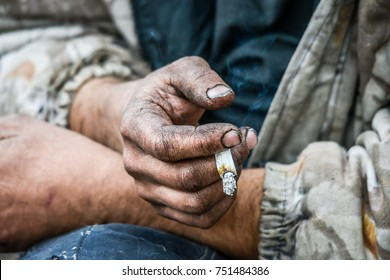 Drug addict homeless junkie with a joint marijuana in dirty hand