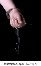 Drug addict man hold an injection and wearing handcuffs