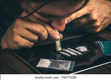 Drug addict man using narcotics, sniffing cocaine lines white powder with rolled dollar banknote. Drug abuse concept