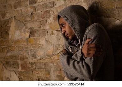 Drug addict posing near brick wall. Addict, breaking, pain, depression, drama, illness, dependence. Ill person hugging himself.