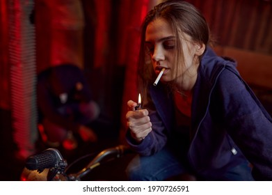 Drug addict woman smokes a cigarette