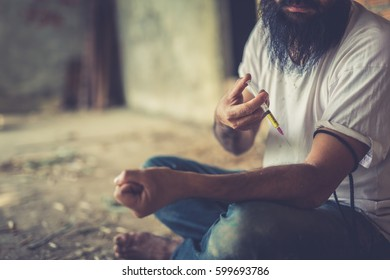Drug addict young man with syringe in action, Drug abuse concept.,