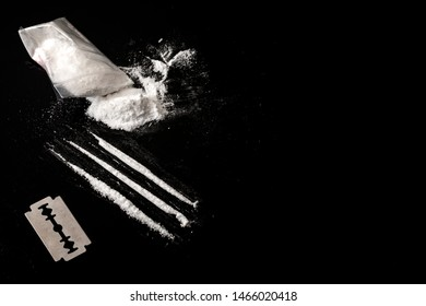 Drug addiction and substance abuse concept theme with lines of cocaine, a small bag with white powder and a blade used to cut each line of narcotics on a dark mirror table with copy space