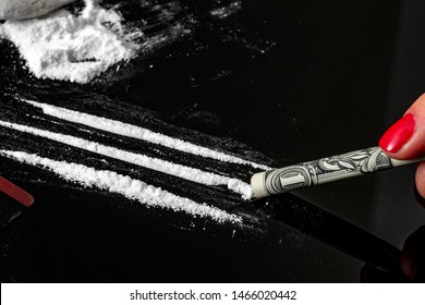 Drug addiction and substance abuse concept theme with close up on a troubled addict using a one dollar bill as a straw to snort a line of cocaine on a dark mirror table next to a pile of white powder