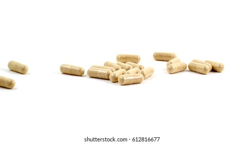 Drug capsule pills with beige medication in pile, isolated