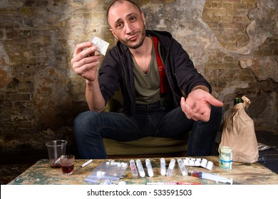 Drug dealer asking for money for narcotics and drugs. Many types of drugs lying on table in front of him. Drugs concept.
