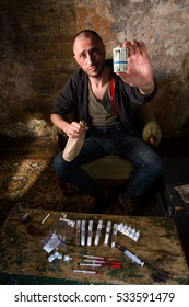 Drug dealer showing profit from selling drugs and injections. Many heavy drugs represented on table in front of him.