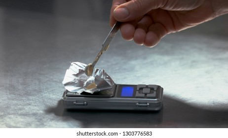 Drug dealer weighing a drug on a digital scale. Hand pouring powder on electronic kitchen scales.