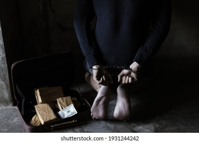 Drug dealers was under arrested by police officer, locked arms trafficking drug guy behind back by using handcuffs Sit on floor It has evidence of Cocaine, heroine or narcotic and illegal money in bag