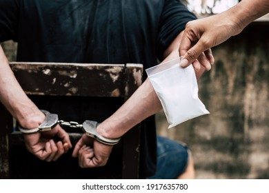 Drug dealers was under arrested and locked the arms bad guy behind his back at the wall by using handcuffs. It has evidence, policeman shows cocaine, heroine or narcotic contains in the plastic bag