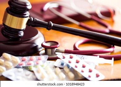 Drug law concept. Judges gavel with  stethoscope  and pills close up