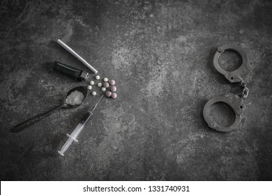 Drug syringe and cooked heroin on spoon and handcuffs . Concept - punishment for possession of narcotic drugs.