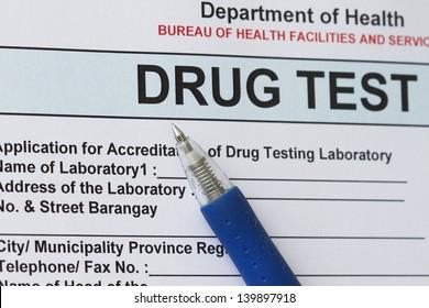 Drug test blank form with blue pen.