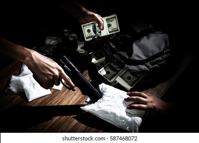 Drug trafficker holding a lot of cash on hand and use gun pushing drugs to the customer in the Drug dealing, concept about the drug problem