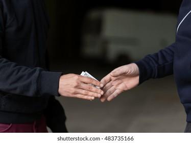 drug trafficking, crime, addiction and sale concept - close up of addict paying money to drug dealer on street