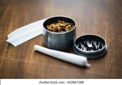 drug use, substance abuse, addiction and smoking concept - close up of marijuana joint and herb grinder