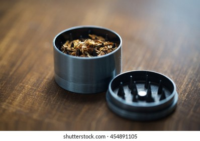 drug use, substance abuse, addiction and smoking concept - close up of marijuana or tobacco and herb grinder