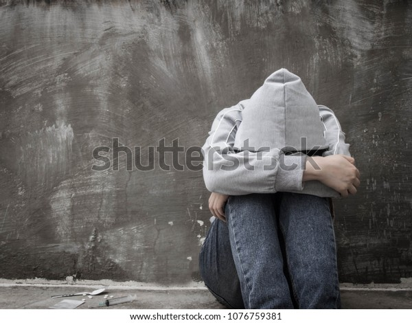 Drugs addiction and withdrawal symptoms concept. Depressed and hopeless teenage girl sitting alone after using drugs and drunk alcohol at abandoned house. International Day against Drug Abuse.