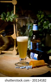 Drugs and Alcohol spread on a kitchen counter with wine, beer and foliage framed neatly in the photo.