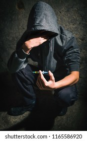 Drugs concept. Disease concept. Drug addict man with syringe using drugs.Dark theme, young guy very stressed, He would drug addiction.