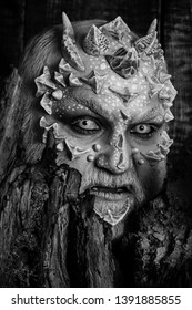 Druid behind old bark on black background. Man with dragon skin and bearded face. Tree spirit and fantasy concept. Monster with sharp thorns and warts. Goblin with horns on head.