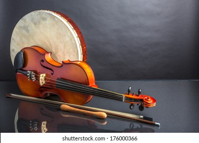Drum and Fiddle. A Irish drum  (bodhran) and a viola on a black background