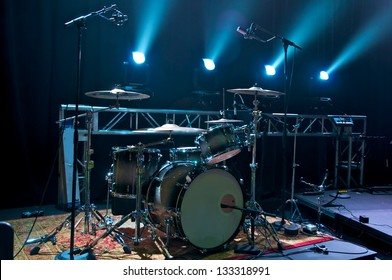 Drum Kit on stage backlit with stage lighting.