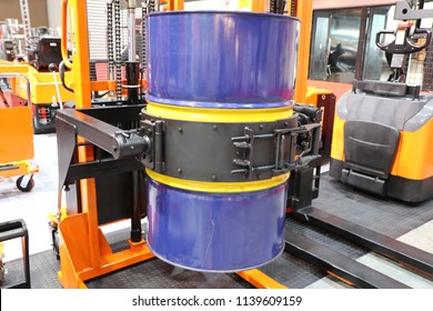 Drum lifted by drum stacker ; selective focus ; industrial warehouse background