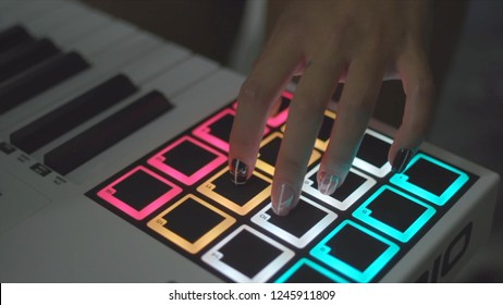 Drum machine in the night club playing live set. Stock. Fingers tapping drum pads on a digital beatmaker close-up. Dj starts playing music set in the club playing the drum machine