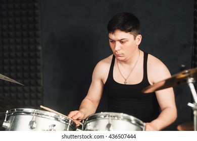 Drum player plays on drum set closeup. Front view on drum player that checks his instrument