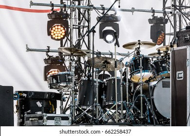 drum set and spotlight system on outdoor stage before concert