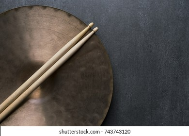 Drum stick and crash cymbal on black table background, top view, music concept