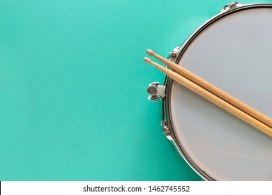 Drum and drum stick on green table background, top view, music concept