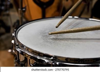 Drum sticks hitting the drum closeup