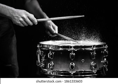 Drum sticks hitting snare drum with splashing water on black background under studio lighting. Black and white. Photo in motion.