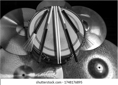 Drum sticks snare drum and cymbals from a bird's eye view in black and white.