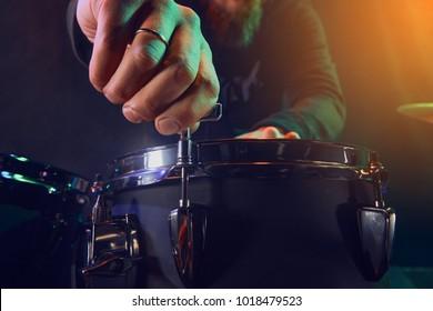 The drummer adjusts the drum set. Scene. Stage light.