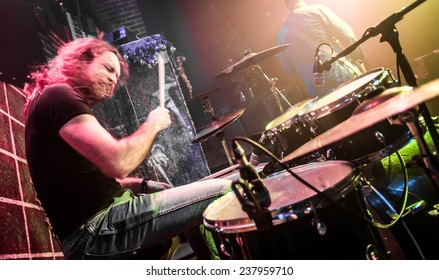 Drummer (blurred motion) playing on drum set on stage. Focus on the drum and microphone. Warning - authentic shooting with high iso in challenging lighting conditions.