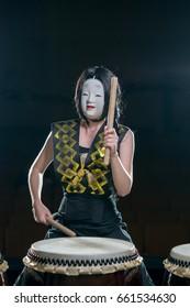 drummer girl in white demon mask with drumsticks, studio concert shot on a dark background.