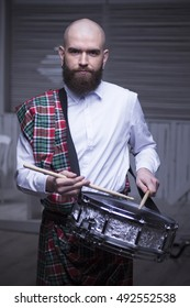 Drummer.The guy holding the drumsticks in his hand. Young man with drumsticks. A bearded man holding a stick in his hands. The guy playing the marching drum. Scottish drummer