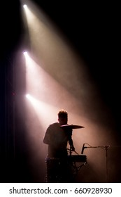 the drummer on the stage in the smoke