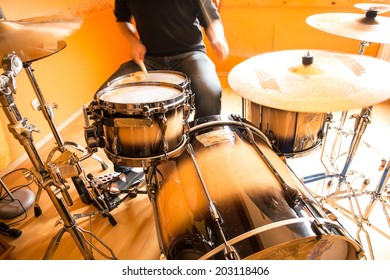 A drummer performing on his Drumset.