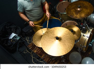 Drummer playing on drum set top view. Live music concert, band recording process.Top view side of electronic modern drum kits set in a small music room