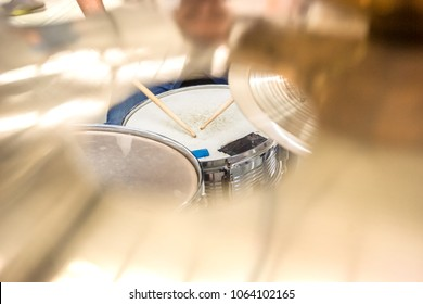 Drummer playing on drum set top view. Live music concert, band during performance. View and look through allong cymballs on snare drum and drum sticks