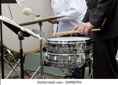 Drummer playing the snare drum, bass drum in background.