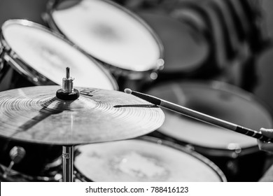Drummer plays the drums. Black and white.