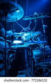 Drummer plays drums, side view, with blue concert lighting